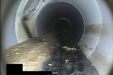 PVC sewer pipeline with mineral deposits before removal with water blast